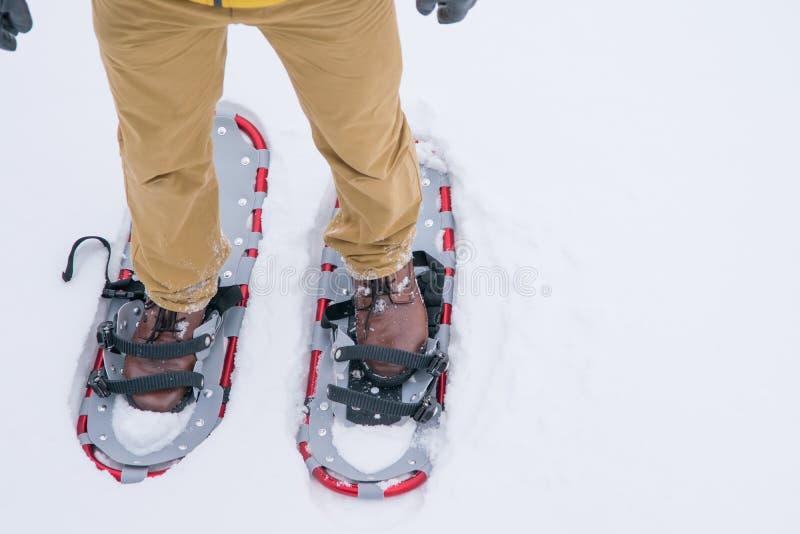 fond d'hiver, une paire de raquettes avec des pieds, se tenant sur la neige blanche pelucheuse images stock