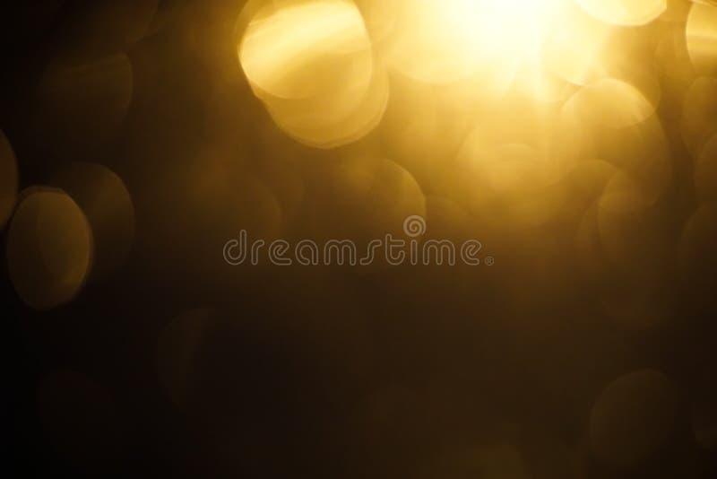 Fond d'obscurité de bokeh de lumière jaune images libres de droits