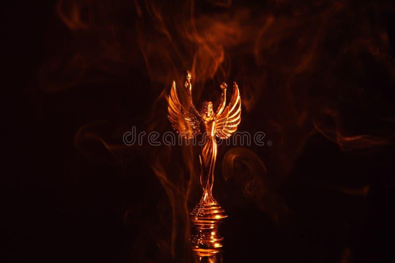 Fond d'obscurité de fumée de statue d'ange d'or photographie stock