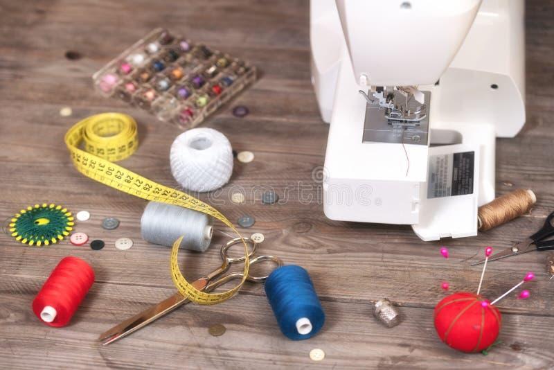 Fond d'ouvrière couturière ou de tailleur avec les outils de couture, les fils colorés, la machine à coudre et les accessoires images libres de droits