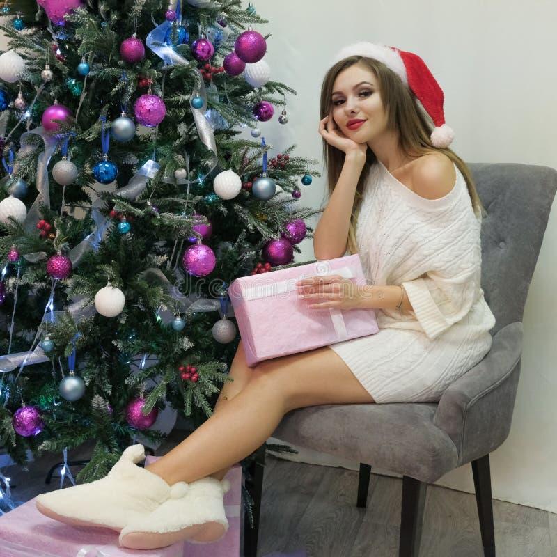 Fond d'une bonne année La belle jeune fille sexy dans un chapeau rouge, un chandail tricoté et des pantoufles de fourrure s'assie photos libres de droits