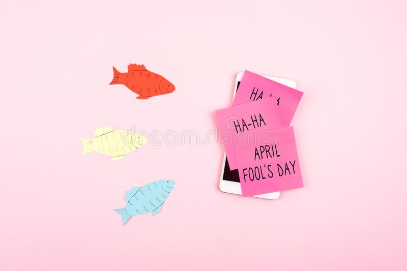 """Fond de célébration de jour d'April Fools """"avec les poissons de papier, le Smartphone et la note collante sur le fond rose Tout d images stock"""