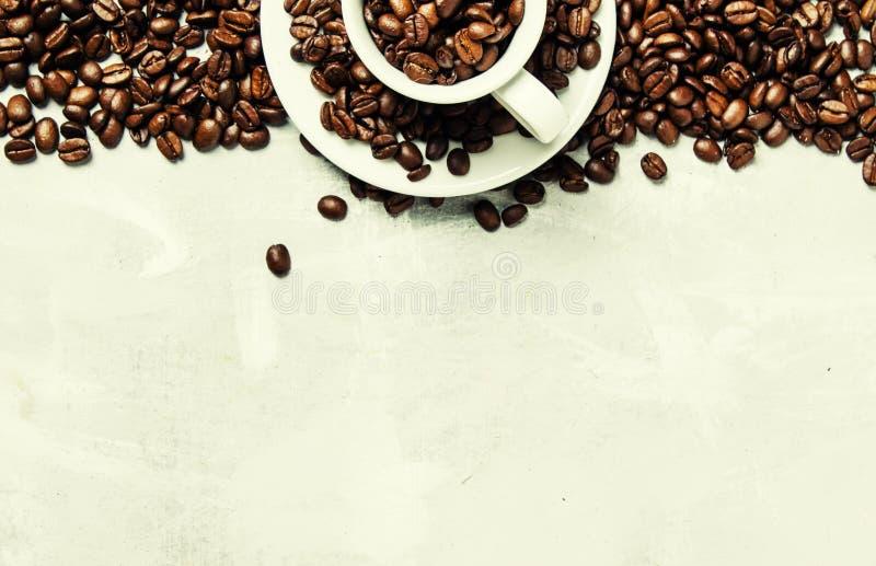 Fond de café, grains de café rôtis dans une tasse blanche, vue supérieure images stock