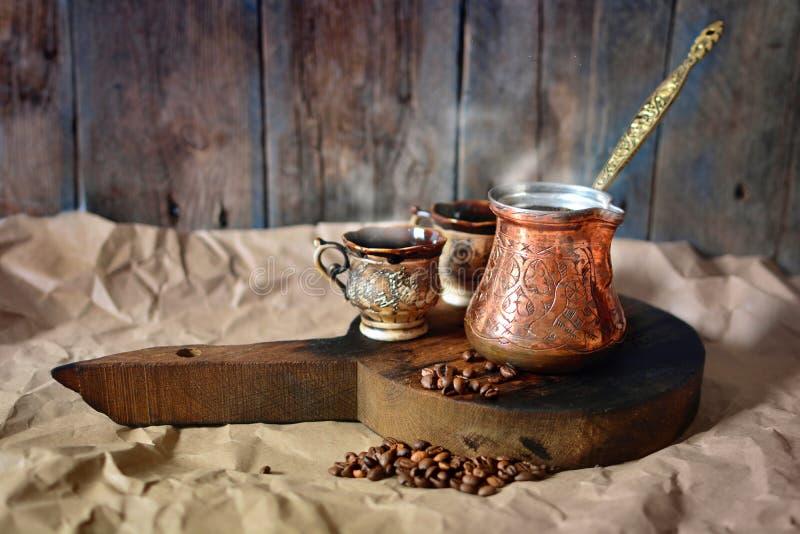 Fond de café turc avec le pot de café, les tasses et les grains de café de cuivre sur un bureau en bois images stock