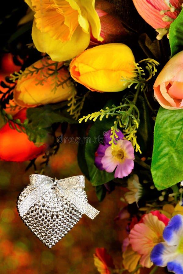 Fond de coeur sur le fond des lumières de bokeh d'arc-en-ciel et des fleurs de jardin Célébration de Saint-Valentin, un coeur  image libre de droits
