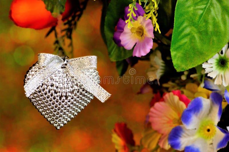 Fond de coeur sur le fond des lumières de bokeh d'arc-en-ciel et des fleurs de jardin Célébration de Saint-Valentin, un coeur  images stock