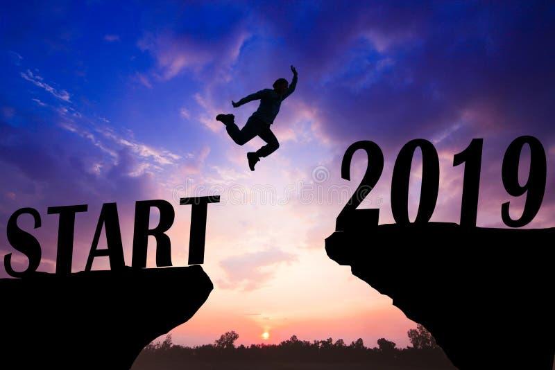 Fond de coucher du soleil de silhouette Un homme saute plus d'à la falaise et au saut à travers entre le début ! et mot 2019 photo libre de droits