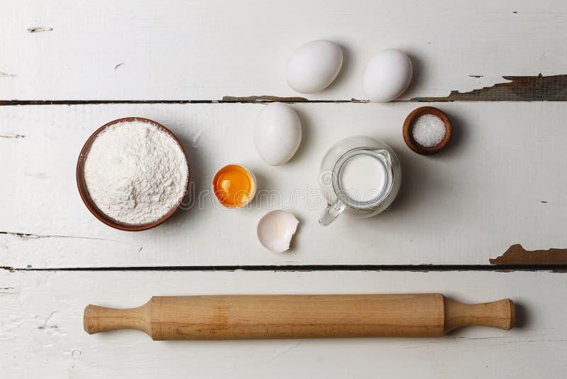 Fond de cuisson Cuisson des ingrédients pour la pâte et la pâtisserie à levure, les oeufs, la farine et le lait sur le bois rusti photo libre de droits