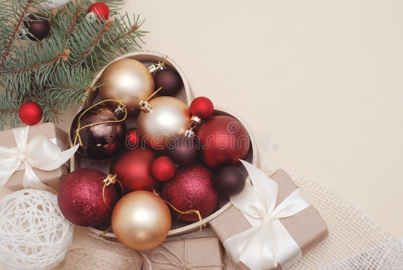 Fond de décorations d'hiver ou de Cristmas - gui rouge de boules et branches vertes de sapin, boîte-cadeau sur l'ivoire chaud photos stock