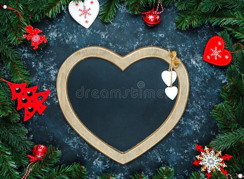 Fond de décorations de Noël ou de nouvelle année : un cadre sous forme de coeur est entouré par des branches d'une nouvelle année images stock