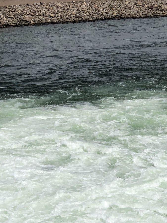 Fond de deux genres d'eau et de rivage rocheux photos stock