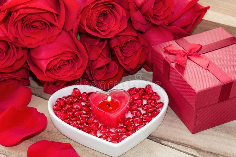 Fond de fête à la Saint-Valentin Un bouquet des roses rouges, d'un boîte-cadeau, d'un plat en forme de coeur et d'une bougie en f images stock