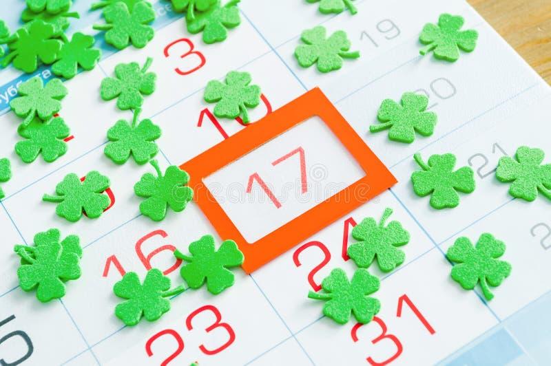 Fond de fête de jour du ` s de St Patrick Les quatrefoils verts couvrant le calendrier d'orange ont encadré le 17 mars images libres de droits