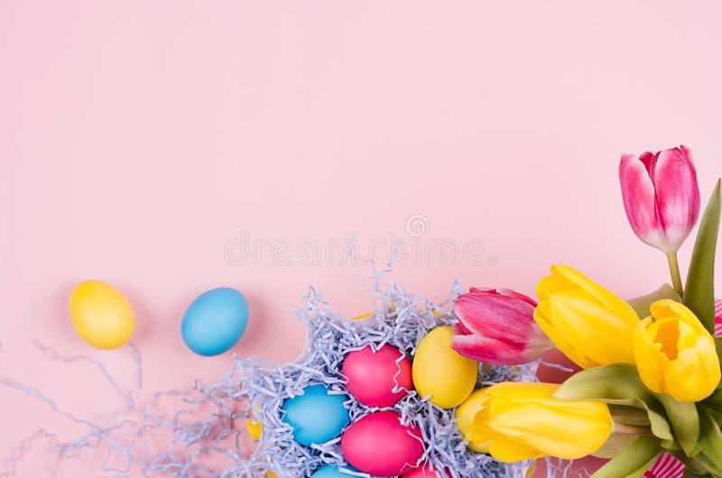 Fond de fête de Pâques de printemps - oeufs multicolores peints faits maison, bouquet de tulipes sur le fond rose-clair en pastel image stock