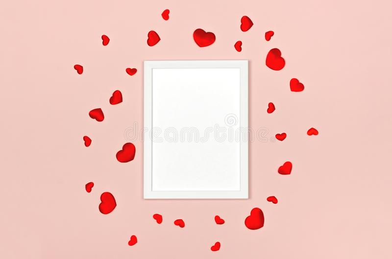 Fond de fête pour la Saint-Valentin avec le cadre blanc vide de photo sur le rose avec les coeurs rouges photos stock