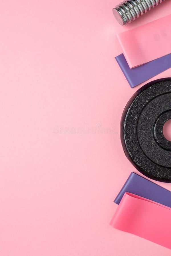 Fond de forme physique L'ensemble de l'athlète avec des haltères et des bandes élastiques pour s'étirer sur un fond rose en paste image stock