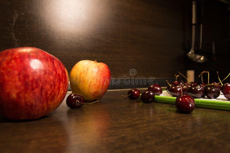 Fond de grandes pommes et de cerises foncées sur la table de cuisine image stock
