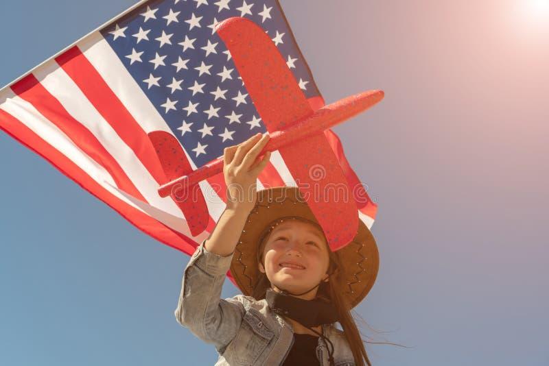 Fond de grunge de l'ind?pendance Day La belle fille dans un chapeau de cowboy sur le fond du drapeau américain tient un avion rou photographie stock