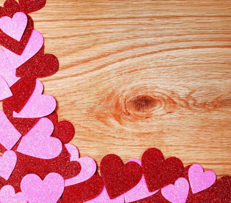 Fond de jour de valentines. Coeurs rouges et roses de scintillement sur en bois photos libres de droits