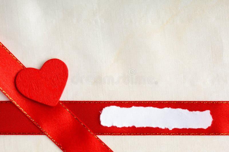 Fond de jour de valentines. Ruban et coeur rouges de satin. images stock