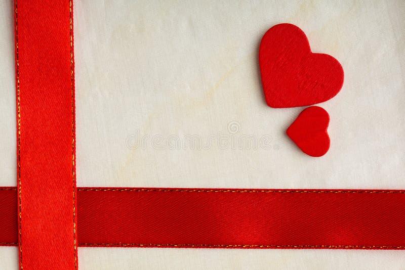 Fond de jour de valentines. Ruban et coeurs rouges de satin. photos stock