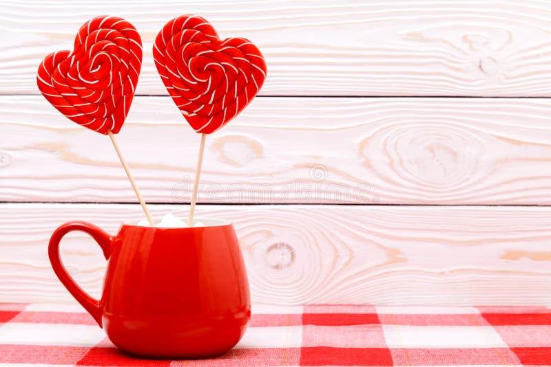 Fond de jour du ` s de Valentine Deux lucettes en forme de coeur dans la tasse rouge sur la nappe à carreaux sur le fond en bois  images libres de droits
