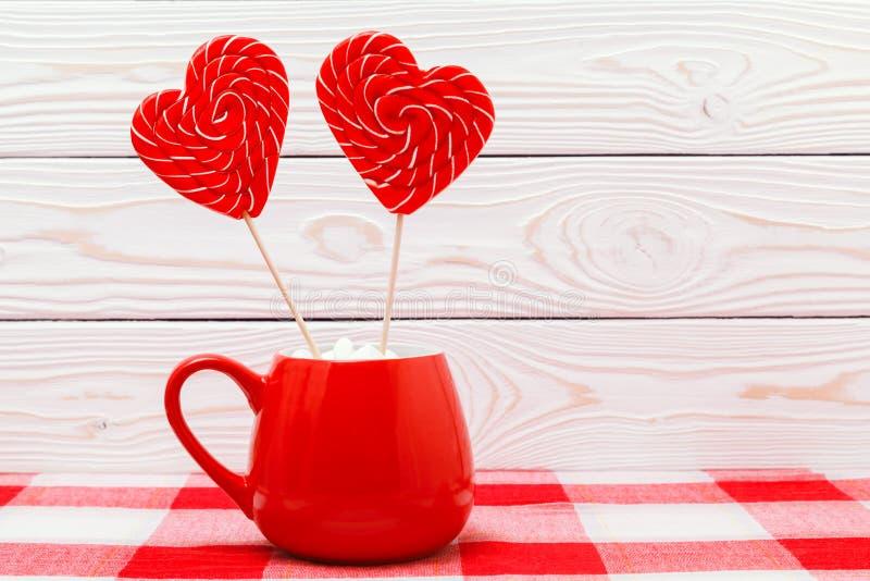 Fond de jour du ` s de Valentine Deux lucettes en forme de coeur dans la tasse rouge sur la nappe à carreaux sur le fond en bois  photographie stock