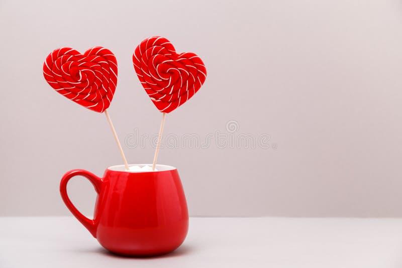 Fond de jour du ` s de Valentine Deux lucettes en forme de coeur dans une tasse rouge, sur un fond gris-clair Carte de voeux image libre de droits