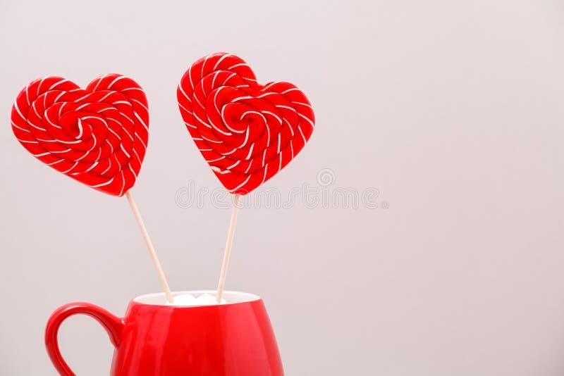 Fond de jour du ` s de Valentine Deux lucettes en forme de coeur dans une tasse rouge, sur un fond gris-clair Carte de voeux photographie stock libre de droits