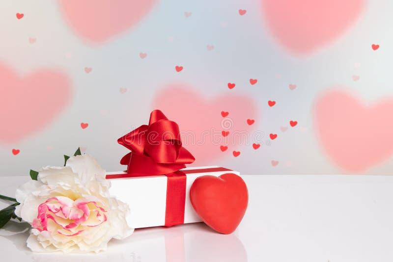 Fond de jour de Valentine Un dessus de table lumineux avec une fleur, un boîte-cadeau et un coeur rouge devant de beaux coeurs ro image libre de droits