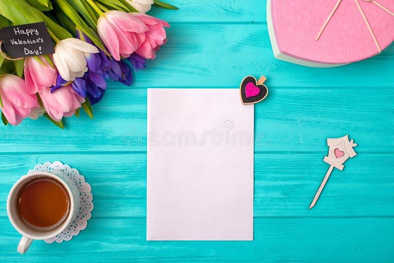 Fond de jour de valentines avec le bouquet des tulipes, d'une carte et d'un cadeau sous forme de coeur photo stock