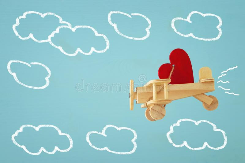 Fond de jour de valentines Avion en bois de jouet avec le vol de coeur dans le ciel image stock
