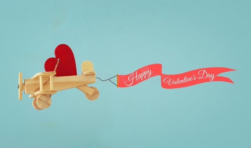 Fond de jour de valentines Avion en bois de jouet avec le vol de coeur et de ruban dans le ciel photographie stock libre de droits