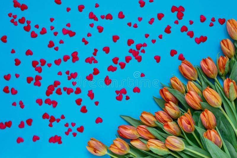 Fond de jour de valentines Bouquet orange de tulipes et coeurs rouges sur le fond bleu Vue supérieure, l'espace de copie photographie stock libre de droits