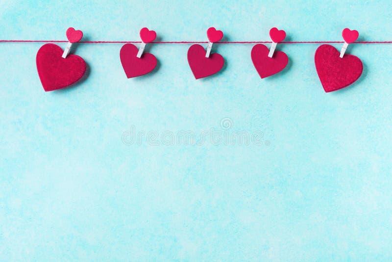Fond de jour de valentines Guirlande des coeurs rouges sur des pinces à linge sur le mur de turquoise photos libres de droits