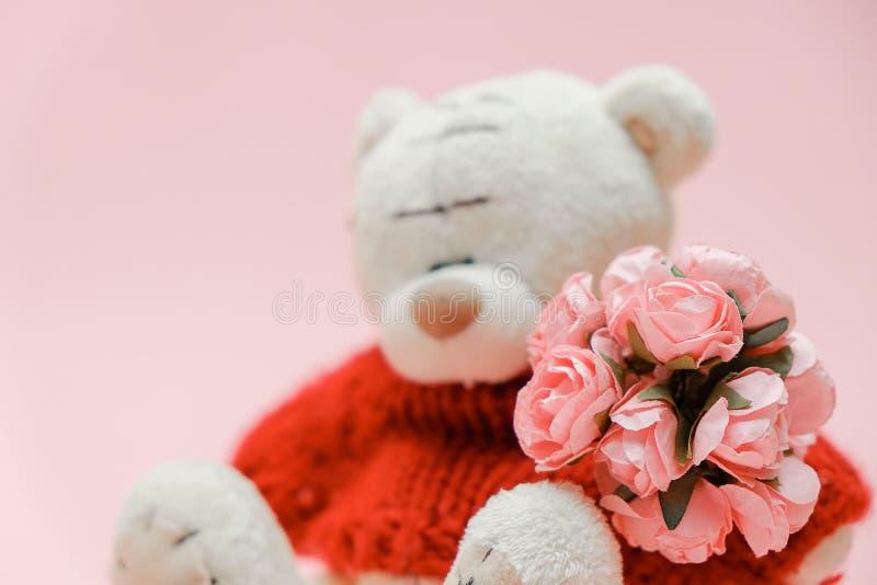 Fond de jour de valentines Jouet mignon d'ours de nounours avec le bouquet des fleurs sur le fond rose 14 février carte de voeux photo stock