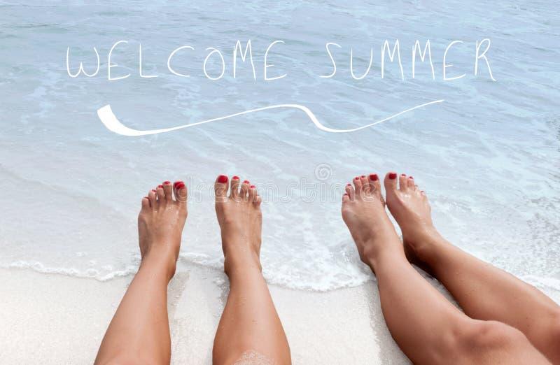 Fond de mer avec marquer avec des lettres l'?t? bienvenu Jambes femelles sur la plage sablonneuse photos stock