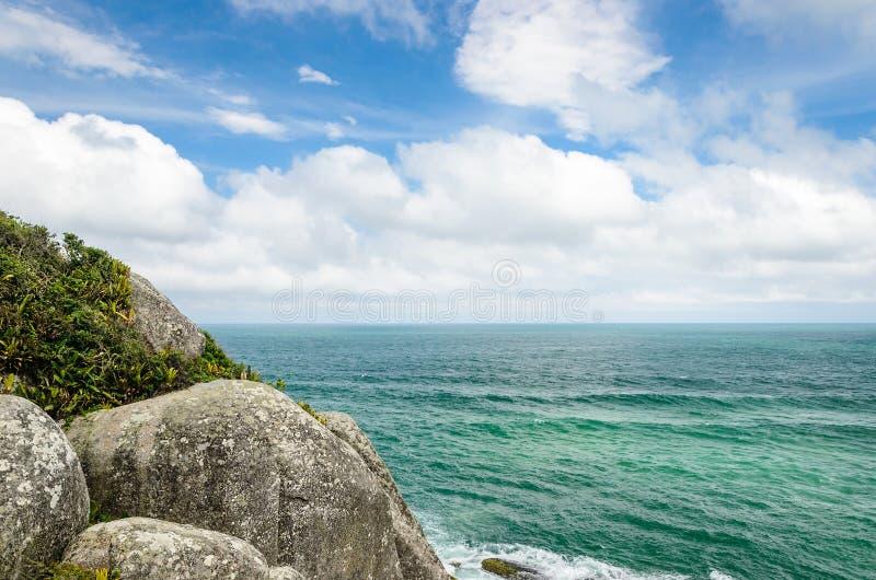 Fond de mer avec quelques grandes pierres et un fond de ciel bleu photographie stock libre de droits