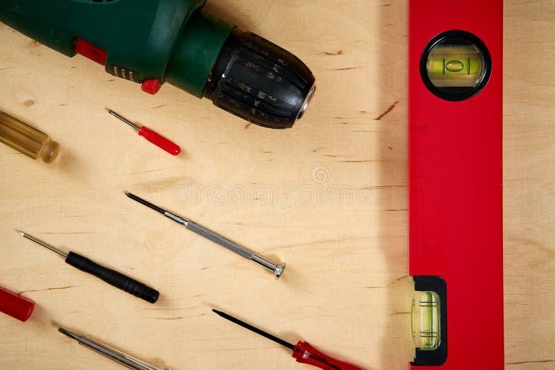 Fond de modèle de divers tournevis et d'une perceuse avec un niveau d'esprit sur une table de travail en bois photo stock