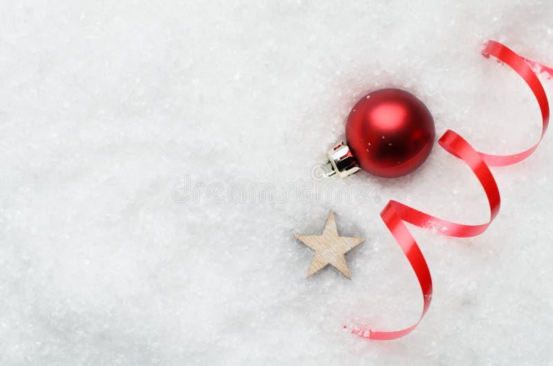 Fond de neige de Noël avec la babiole rouge, le remous et l'étoile photographie stock