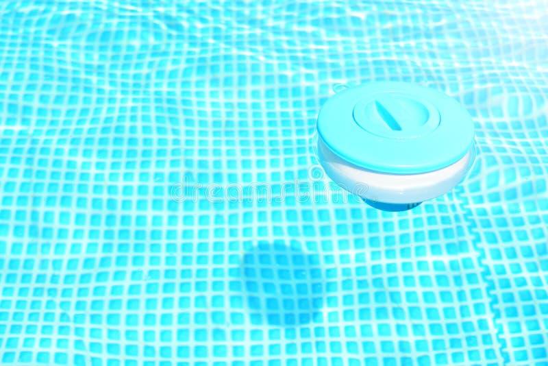 Fond de nettoyage de produits chimiques de piscine Le distributeur de flottement de comprimé de chlore pour des piscines se situe photos libres de droits
