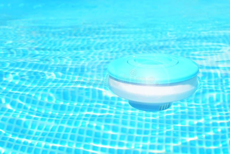 Fond de nettoyage de produits chimiques de piscine Le distributeur de flottement de comprimé de chlore pour des piscines se situe photos stock