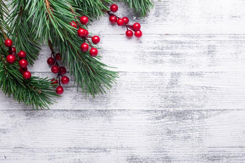 Fond de Noël avec des branches d'arbre et des baies de houx Table en bois blanche photos libres de droits