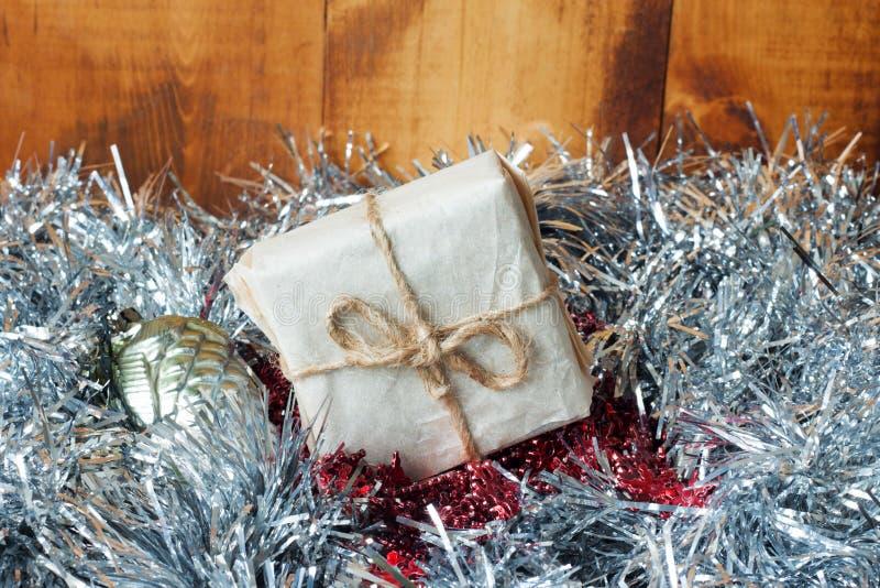Fond de Noël avec des décorations et des boîte-cadeau sur le conseil en bois avec la tresse argentée photos stock