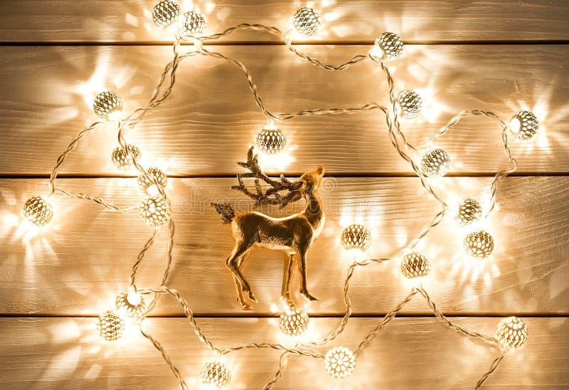 Fond de Noël avec des lumières de guirlande et des cerfs communs d'or photographie stock libre de droits
