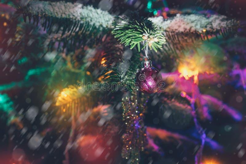 Fond de Noël avec l'arbre de Noël dans la neige décorée des jouets et des lumières colorées photographie stock