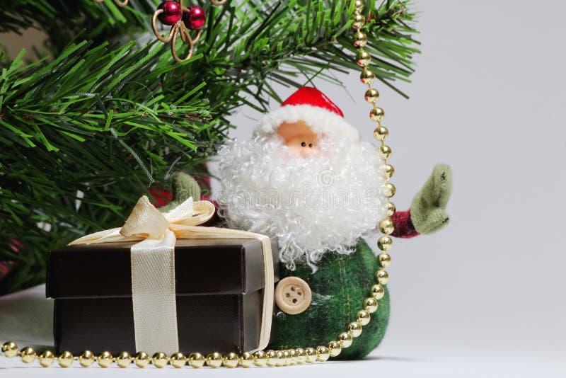 Fond de Noël avec l'arbre de Noël, Santa Claus, boîte de brun de cadeau pour un anneau avec un ruban beige et des perles d'or photo stock
