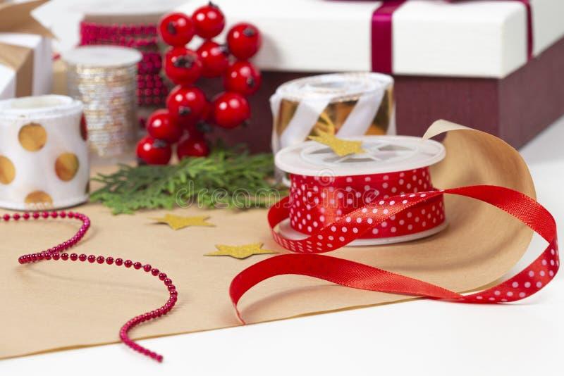 Fond de Noël avec la boîte actuelle de cadeaux, papier d'emballage, rubans, arcs sur la table blanche photo libre de droits