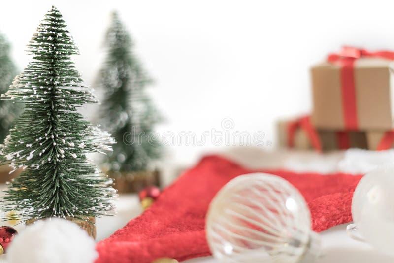 Fond de Noël avec la boule de Noël, les boîte-cadeau, l'arbre et le chapeau de Santa sur le fond blanc photos libres de droits