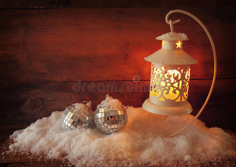 Fond de Noël avec la lanterne, la babiole et la neige blanches au-dessus du fond en bois image libre de droits